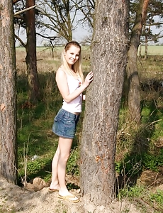 A tree hugging teenage hotty gropes her wet love button outside